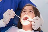 Pediatric dentist examining her young patient in dental clinic