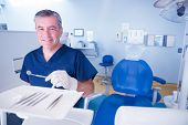 Dentist in blue scrubs smiling at camera holding tools at the dental clinic