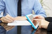 Businesswoman Is Working With Tablet Pc And Businessman Is Writing A Document
