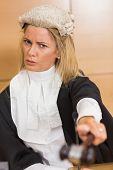 stock photo of court room  - Stern judge pointing her hammer in the court room - JPG