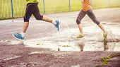 stock photo of rainy weather  - Young couple jogging on asphalt in rainy weather - JPG