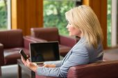 Blonde businesswoman using her phone in office building