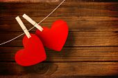 Hearts hanging on line against overhead of wooden planks