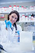 Smiling female scientist using a pipette in hospital