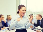 business, technology and education concept - screaming businesswoman with smartphone in office