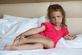 Angry little girl lying on the bed.