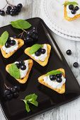 picture of mountain-ash  - canape with cottage cheese black berries of mountain ash and fresh mint leaves on a white wooden background - JPG
