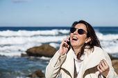 Attractive Woman Talking By Phone To The Sea