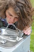 Teenager Drinks From A Drinking Fountain