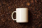stock photo of mug shot  - Closeup shot of white mug against coffee beans with anise stars lying like steam  - JPG