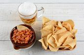 High angle shot of a bowl of corn chips a crock full of fresh salsa and mug of beer on a whitewashed rustic wood table. Horizontal format.