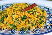 foto of cumin  - traditional Indian dish called khichdi. Included rice mung bean cumin and curry with cinnamon stick on plate with asian ornament