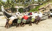 Fishermen Pushing The Fishing Boat On The Beach