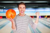 image of bowling ball  - Cheerful young man holding a bowling ball and keeping arms raised while standing against bowling alleys - JPG