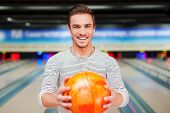 picture of bowling ball  - Cheerful young man stretching out a bowling ball and smiling while standing against bowling alleys - JPG