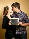 Couple Kissing And And Holding Board With Declaration Of Love
