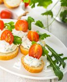 image of canapes  - canapes with cheese and venetables on a light background with arugula and cilantro. Selective focus