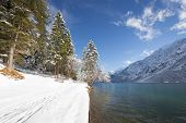 winter footpath tracks in snow at cold lake in tirol austria