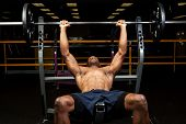 stock photo of work bench  - Weight lifter at the bench press lifting a barbell on an incline bench - JPG