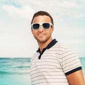 Young Smiling Man In White Sunglasses On Sea Coast