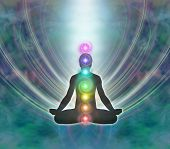 image of soul  - Silhouette of a man in lotus meditation position with Seven Chakras on blue background with kundalini energy flowing downwards - JPG