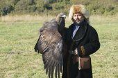 Mongolian hunter holds golden eagle, circa Almaty, Kazakhstan.