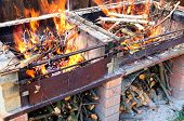 Burning firewood in self made brick and metal brazier or grill