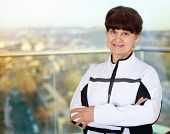 Pension age good looking woman smiling in sport costume