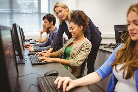 image of teachers  - Attractive teacher helping her student in computer class at the university - JPG