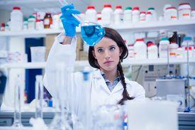 picture of beaker  - Chemist raising beaker of blue liquid in lab - JPG