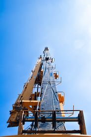 foto of boom-truck  - truck crane boom with hooks and scale weight above blue sky - JPG