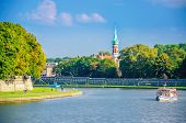 stock photo of old boat  - Vistula river with tourist boat and old Jewish district in background Krakow Poland - JPG