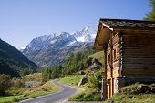 pic of quaint  - Quaint Wood Cabin Beside Paved Single Lane Mountain Road Through Snow Capped Alps Valais Switzerland - JPG