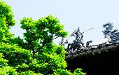 foto of garden sculpture  - Chinese sculptures that protect the building on top of a asian style roof at Yuyuan Gardens in Shanghai China on a bright sunny day - JPG