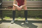 image of sitting a bench  - A young woman wearing knee high socks is sitting on a park bench - JPG