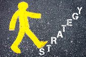 picture of pedestrians  - Yellow pedestrian figure on the road walking towards STRATEGY - JPG