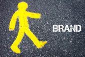 image of pedestrians  - Yellow pedestrian figure on the road walking towards BRAND - JPG