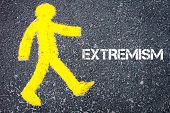 stock photo of pedestrians  - Yellow pedestrian figure on the road walking towards EXTREMISM - JPG