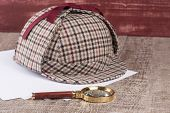 foto of private investigator  - Paper sheets and magnifying glass on Old Wooden table - JPG