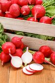 stock photo of wooden crate  - Macro of fresh sliced red radish in wooden crate - JPG