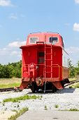 picture of caboose  - An old red caboose on a track under blue skies - JPG