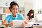 stock photo of schoolgirl  - Smiling Asian schoolgirl using digital tablet in the class - JPG