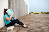 picture of shy girl  - Shy college girl covering her face with a textbook - JPG