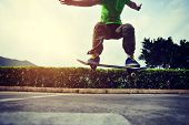 stock photo of parking lot  - young woman skateboarder doing ollie trick at parking lot - JPG