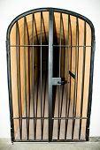 image of lockups  - a locked black door with metal bars in a corridor of a prison - JPG