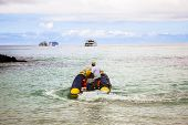 stock photo of outboard  - inflatable boat carrying tourists yachts in Galapagos Islands - JPG