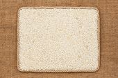 picture of sackcloth  - Frame made of rope with rice grains on sackcloth as background texture - JPG