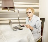 stock photo of old lady  - Old European blond lady working with notebook at home - JPG