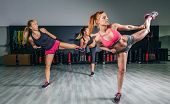 foto of training gym  - Group of beautiful women in a hard boxing class on gym training high kick - JPG