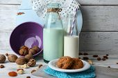stock photo of caw  - Milk in glassware with walnuts and cookies on background - JPG